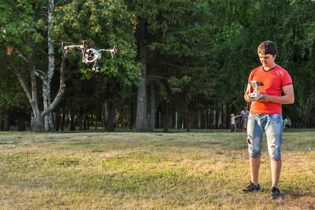 自然の中でリモートコントロールによるドローンの飛行またはホバリングを操作する男