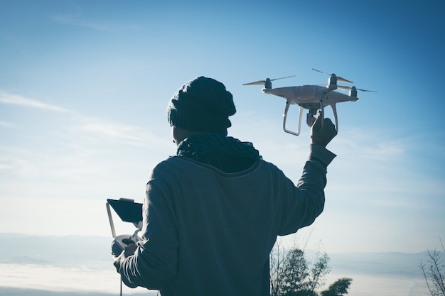 Man operating a drone with remote control. silhouette against colorful sunset.