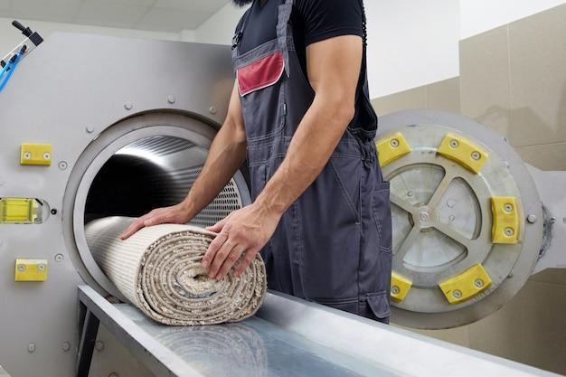 Человек управляет сушильной машиной для чистки ковров. профессиональная чистка ковров