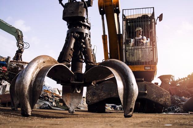 폐차장에서 고철을 들어 올리는 데 사용되는 굴삭기 산업 기계를 작동하는 남자