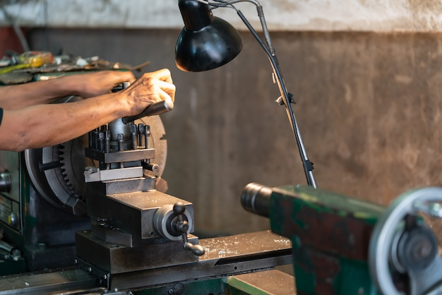 Man operating lathe grinding machine - metalworking industry concept.