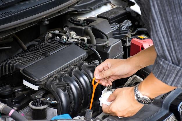 남자 또는 자동차 정비사는 여행하기 전에 자동차 엔진 오일과 유지 보수를 확인합니다.