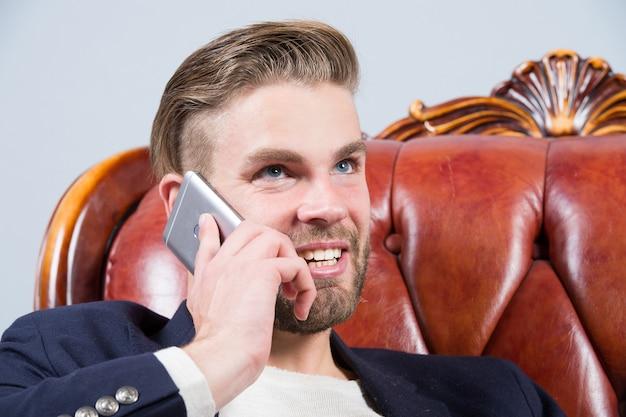 男性またはビジネスマンは笑顔でソファの上のスマートフォンで話します。ビジネスコミュニケーションの概念。起業家精神、新技術、現代生活。