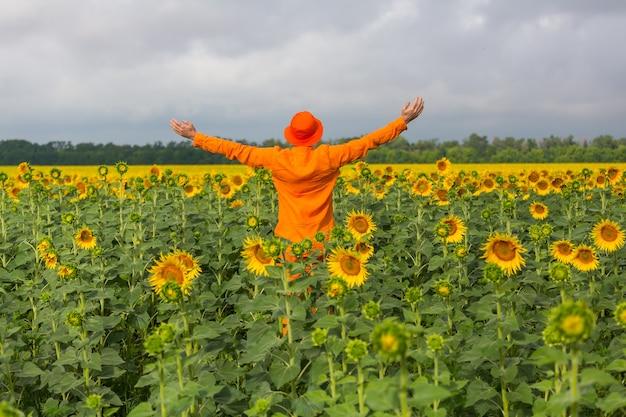 Man in orange clother in sunner sunflowers field