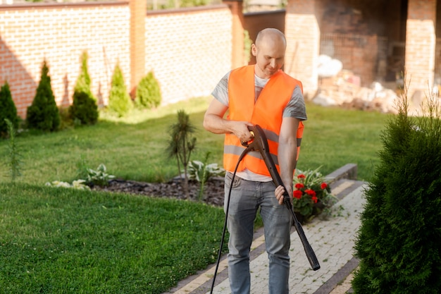 A man in an orange vest cleans a tile of grass in his yard near the house.