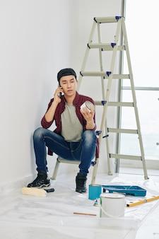 Человек, заказывающий белую краску по телефону