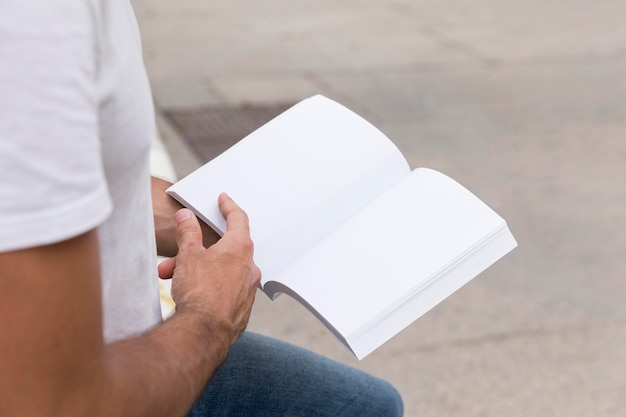 Man outdoors holding book
