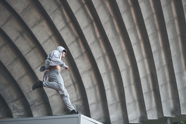 The man outdoors practices parkour, extreme acrobatics.