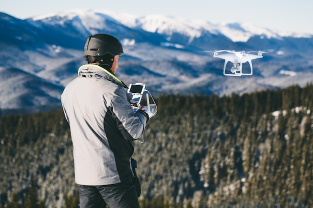 Man outdoors with remote control flying a drone in the mountains