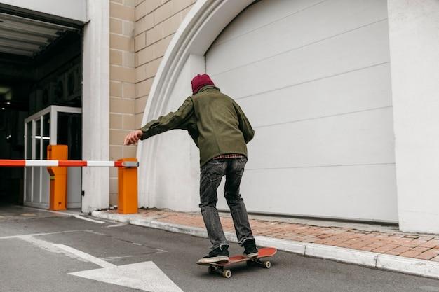 街でスケートボードを持って外の男