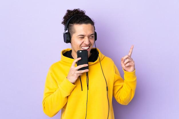 모바일 및 노래와 격리 된 보라색 듣는 음악에 남자