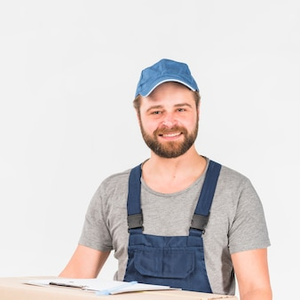 Man in overall and cap smiling