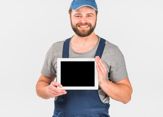 Man in overall holding tablet with blank screen