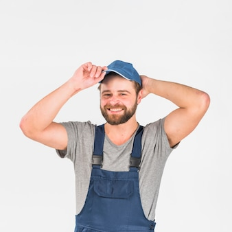 Man in overall putting cap on head