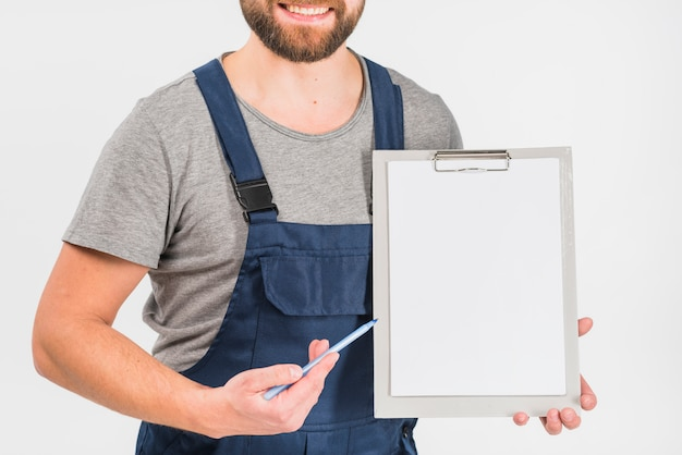 Man in overall showing clipboard with blank paper