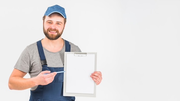 Man in overall showing clipboard with paper