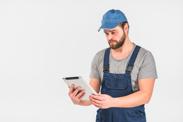 Man in overall using tablet
