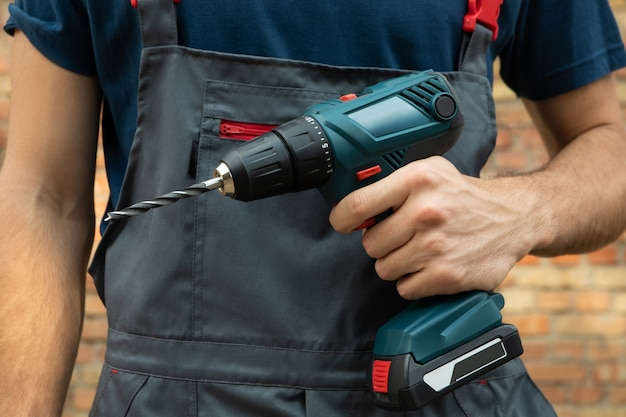 Man in overalls holds cordless drill on brick wall