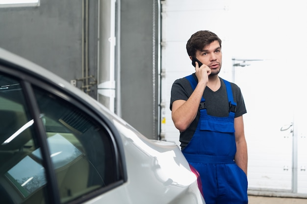 A man in overalls is standing by the car and talking on the phone