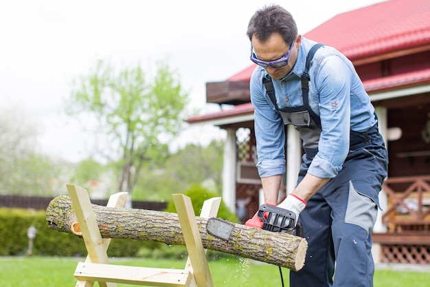 Man in overalls saws a tree on sawhorses in courtyard with a chainsaw