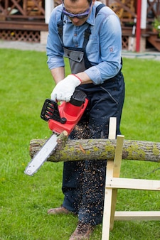 Man in overalls saws wood with chain saw using sawhorse on green lawn