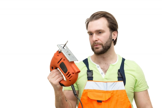 Man in overalls with a jigsaw