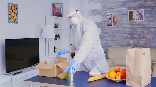Uomo che imballa il cibo in una scatola per la consegna indossando una tuta protettiva contro il covid-19 in tempo di quarantena