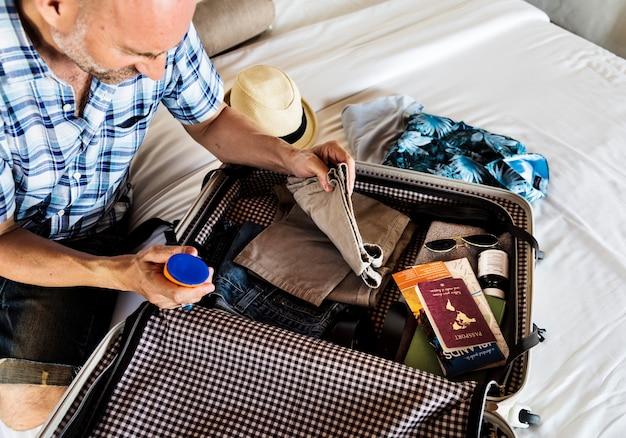 Uomo che fa le valigie per una vacanza