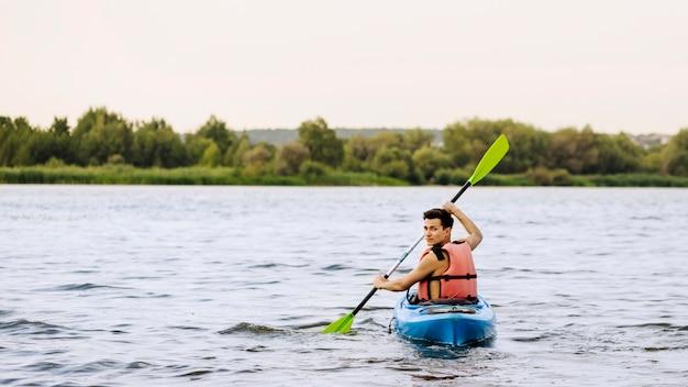Человек весла каякинг над озером, оглядываясь назад