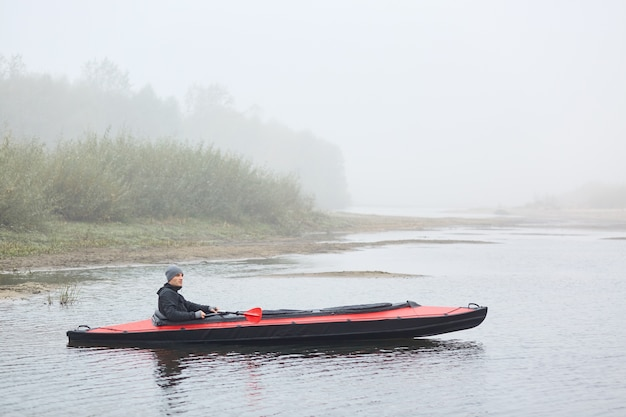 Man paddling canoe on cold day in lake, having rest in active way, sitting in boat and looking at beautiful nature, wearing jacket and cap, water sport