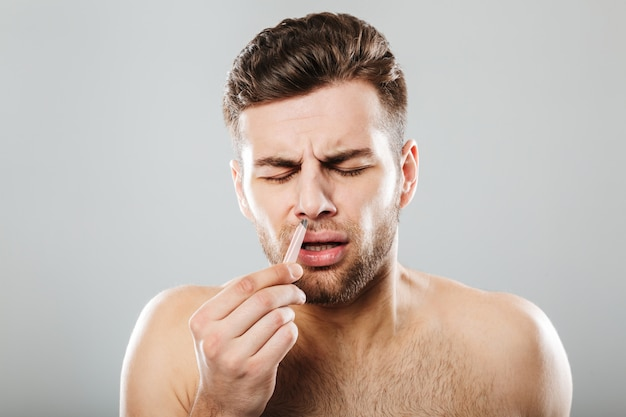 Man in pain removing nose hair with tweezers