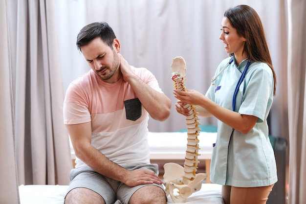 Man in pain sitting on hospital bed and holding neck. next to him standing doctor and holding model of spine and talking to him.