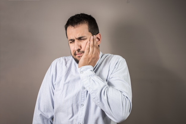 Man in pain throwing his hand to his face
