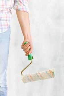 壁を塗るための汚れたローラーを持ったカジュアルな服装の男性/画家