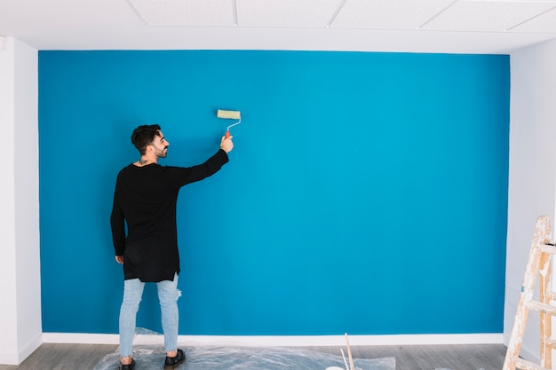 Man painting blue wall