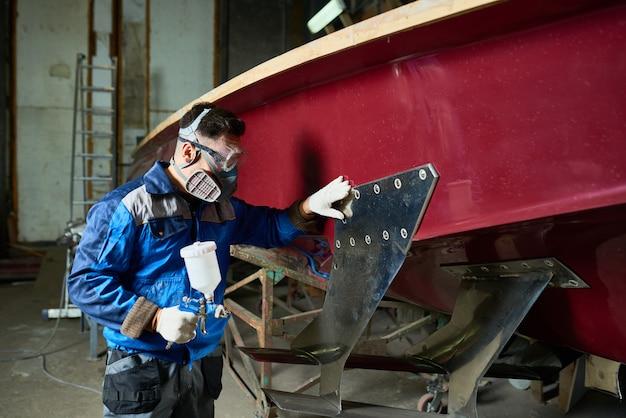 Человек, рисующий лодки в яхтенной мастерской