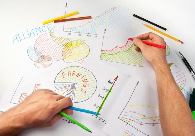 Man painting business diagrams on papers with soft-tip pen