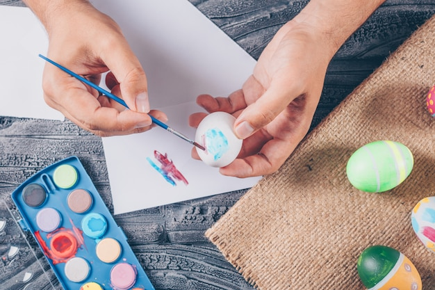 Man painting an egg with easter eggs on sack and paint on dark wooden background