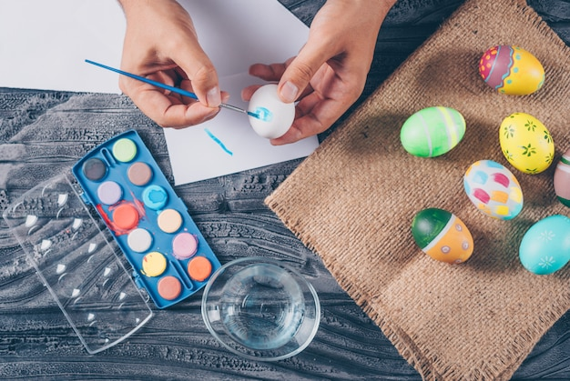 Man painting an egg with easter eggs on sack and paint top view on dark wooden background