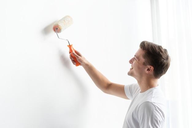 L'uomo dipinge il muro di bianco