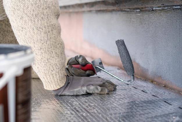Мужчина красит домашний цоколь валиком. закройте серой краской завальцовки на цоколе здания. ремонт дома