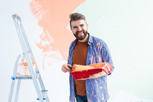 家の内壁を塗る男