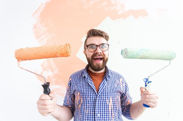 Человек рисует внутреннюю стену нового дома