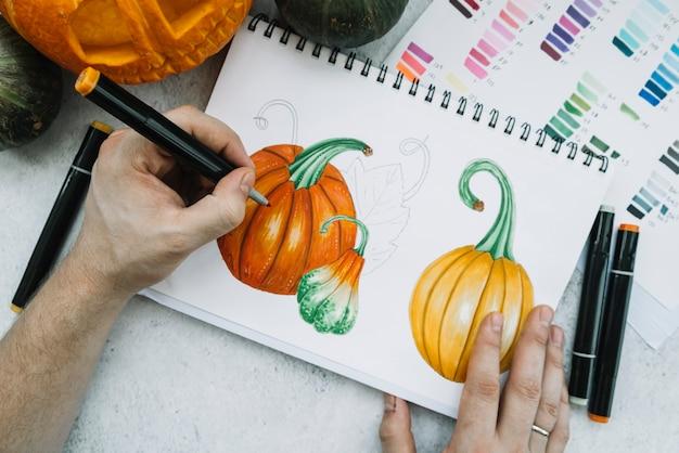 Man painting pumpkin with felt-tip pen