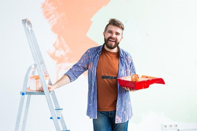 ペイントローラーで壁を塗っている男。彼女の新しいアパートで壁を描いている男の肖像画