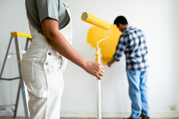 Человек красит стены желтым