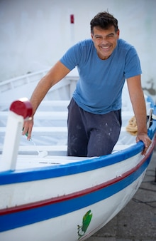 Man painting traditional row boat with brush