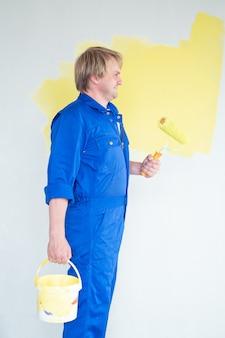 롤러 리노베이션 수리 및 재장식 개념으로 노란색으로 벽을 칠하는 남자