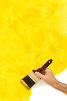 Man painting a  wall in yellow