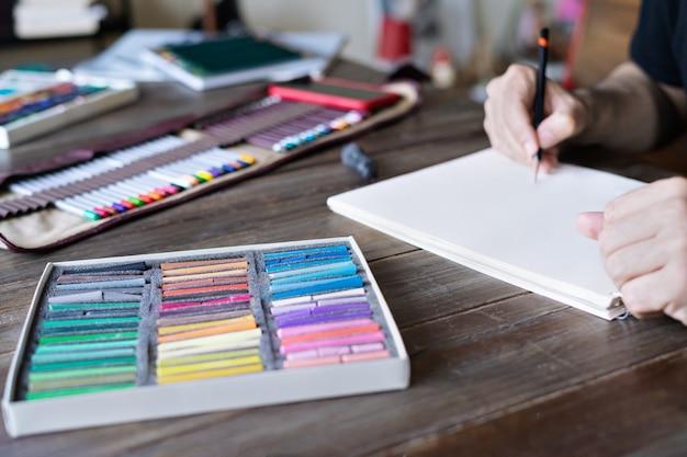 男は白い紙に鉛筆とパステルクレヨンチョークでペイントします。パステルチョークと木製のテーブルに色鉛筆のボックス